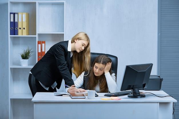 Dwie dziewczyny przy białym biurku w biurze omawiają chwile pracy w biurze