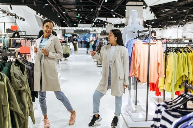 Dwie dziewczyny przymierzające płaszcze w sklepie odzieżowym. kobiety robiące zakupy w butiku, miłośnicy zakupów, kupujący szukający ubrań na wieszakach