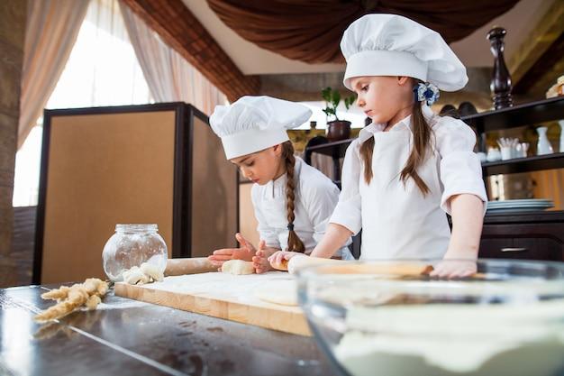 Dwie dziewczyny robią ciasto na mąkę.
