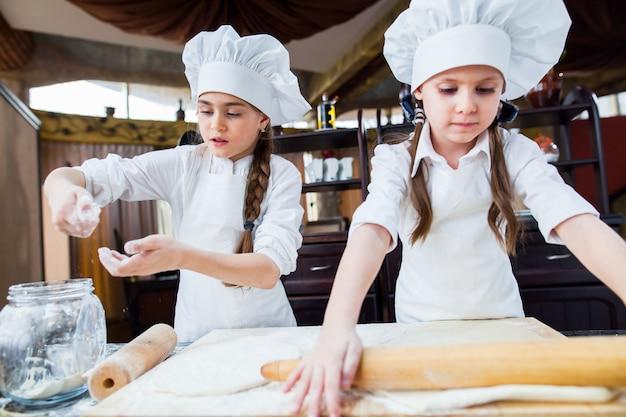 Dwie dziewczyny robią ciasto z mąki.