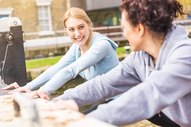 Dwie dziewczyny robią ćwiczenia rozciągające na świeżym powietrzu w londynie