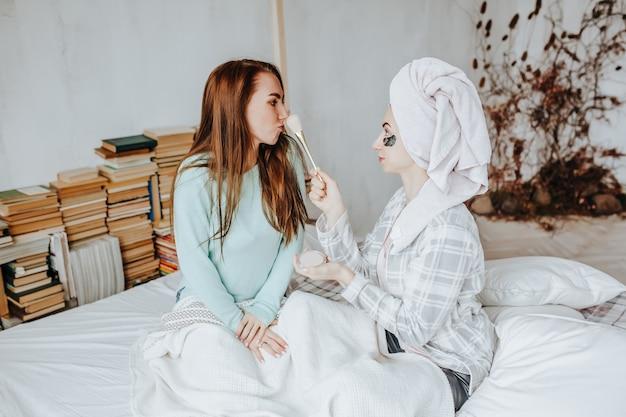 Dwie dziewczyny robią maski i plastry dla urody twarzy i włosów