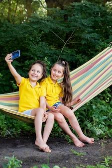 Dwie dziewczyny robią selfie na telefonie na hamaku