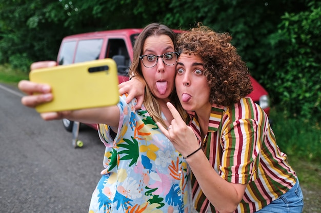 Dwie dziewczyny robiące sobie selfie z telefonem wystawiającym języki podczas podróży