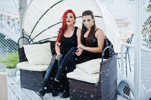 Dwie dziewczyny siedzą na kanapie w deszczu