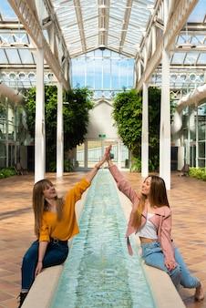 Dwie dziewczyny siedzą na skraju fontanny z wodą w jasnej szklarni