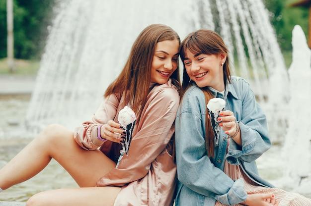 Dwie dziewczyny siedzą przy fontannie i idą lody.