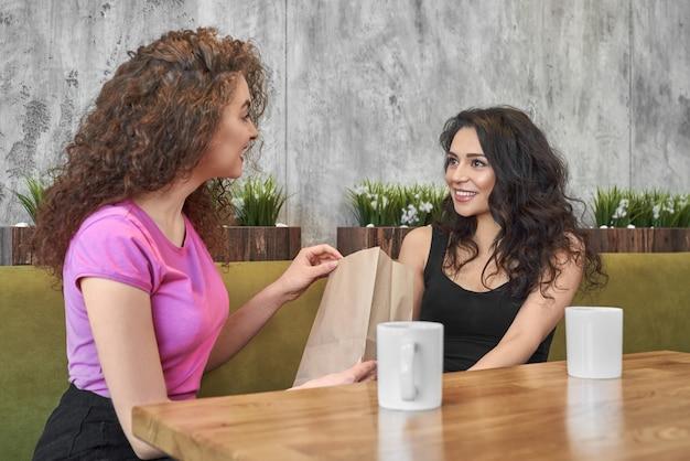 Dwie dziewczyny siedzą w kawiarni, dając prezent.