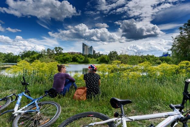 Dwie dziewczyny siedzą wygodnie przy rowerach