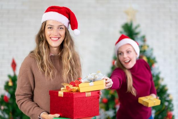 Dwie dziewczyny śmieją się i dzielą świąteczne prezenty. obchody bożego narodzenia i przyjęcie noworoczne