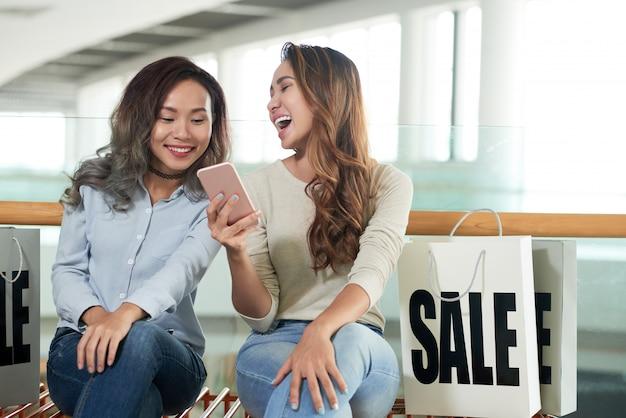 Dwie dziewczyny śmieją się z zabawnego wideo przez telefon