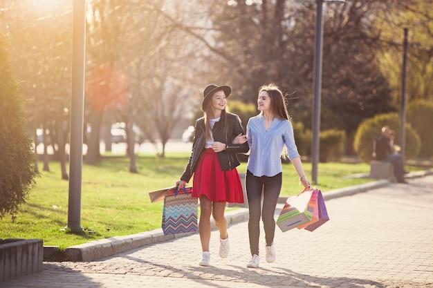 Dwie dziewczyny spaceru z zakupami na ulicach miasta