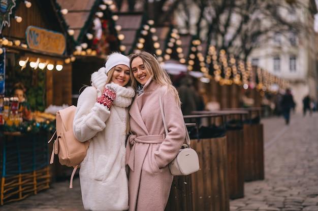 Dwie dziewczyny stoją na jarmarku bożonarodzeniowym ozdobionym świątecznymi girlandami