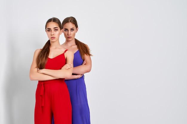 Dwie dziewczyny stojące w studio w eleganckich kolorowych kombinezonach na białym tle