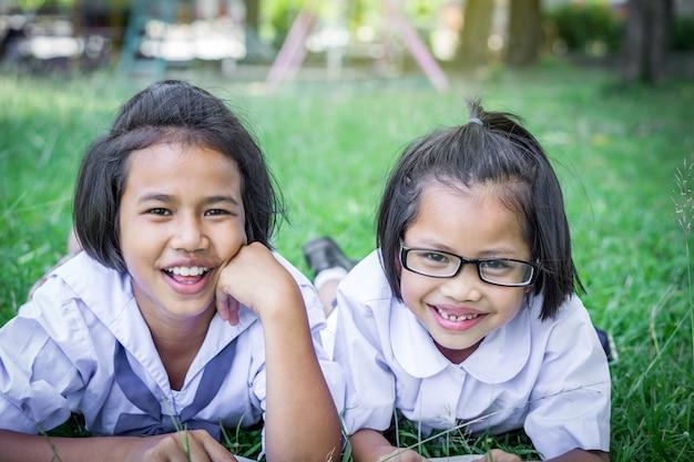 Dwie dziewczyny studentów ustanawiające na trawie w szkole