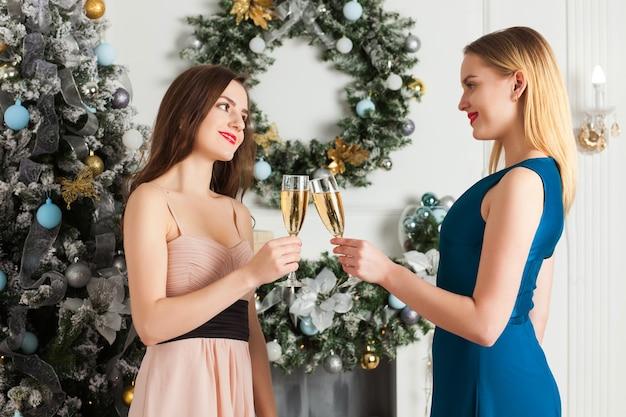 Dwie dziewczyny trzymając kieliszki szampana. świętuj nowy rok, boże narodzenie. obok choinki