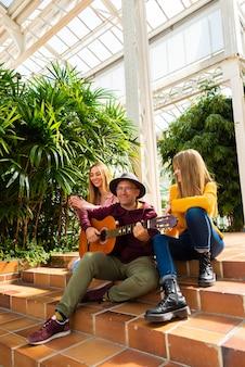 Dwie dziewczyny uśmiechają się, podczas gdy muzyk gra na gitarze i śpiewa