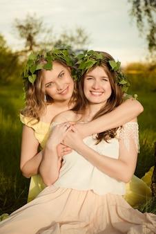 Dwie dziewczyny uśmiechając się i przytulając na zewnątrz latem