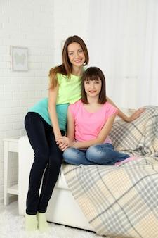 Dwie dziewczyny uśmiechające się na wewnętrznej powierzchni domu