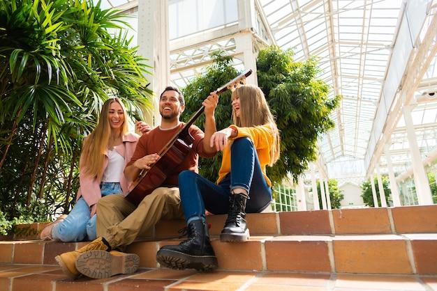 Dwie dziewczyny uśmiechnięte, podczas gdy muzyk gra na gitarze