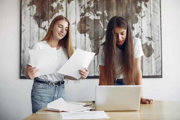 Dwie dziewczyny w białych koszulkach pracujących w biurze