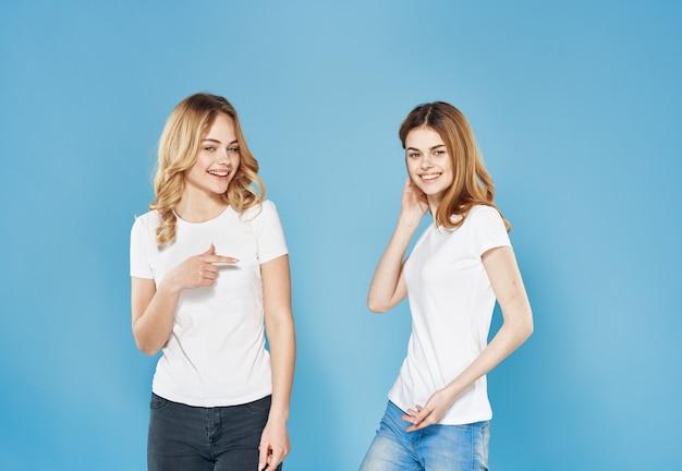 Dwie dziewczyny w białych koszulkach przyjaźń emocje niebieskie tło
