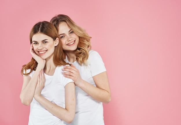 Dwie dziewczyny w białych koszulkach przytulają radość komunikacji przycięty widok