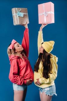 Dwie dziewczyny w ciąży z prezentami w ręce na niebieskim tle na białym tle.