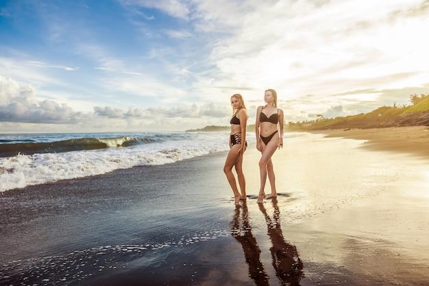 Dwie dziewczyny w czarnych strojach kąpielowych stoją na plaży o zachodzie słońca