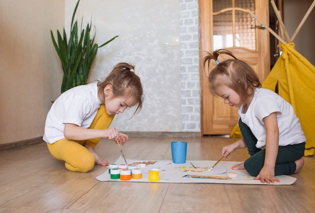 Dwie dziewczyny w jasnych ubraniach siedzą na podłodze na kolanach i entuzjastycznie rysują jaskrawymi akwarelami.