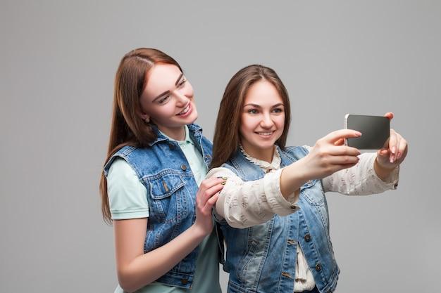 Dwie dziewczyny w kurtkach denum robi selfie
