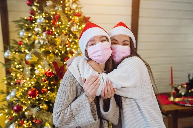 Dwie dziewczyny w maskach ochronnych, patrząc w kamerę. boże narodzenie podczas koronawirusa, koncepcja