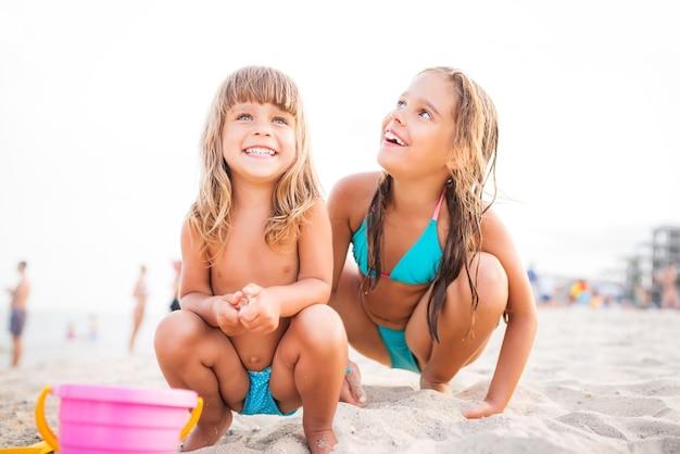 Dwie dziewczyny w niebieskich strojach kąpielowych bawiące się na plaży z zabawkami dla dzieci siedząc w piasku. na białym tle na jasnym tle