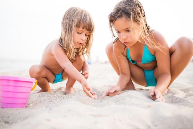 Dwie dziewczyny w niebieskich strojach kąpielowych, grając na plaży z zabawkami dla dzieci, siedząc w piasku.