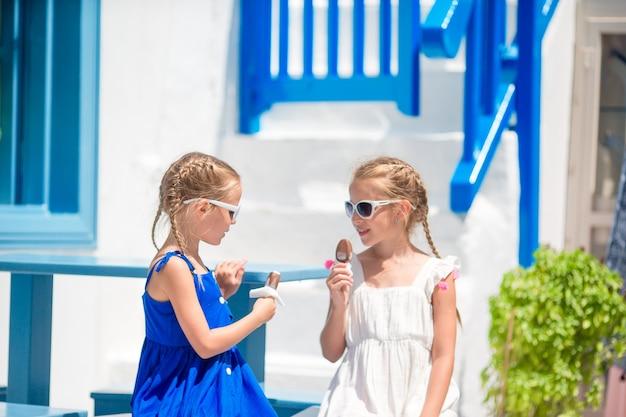 Dwie dziewczyny w niebieskich sukienkach siedzą na niebieskich krzesłach