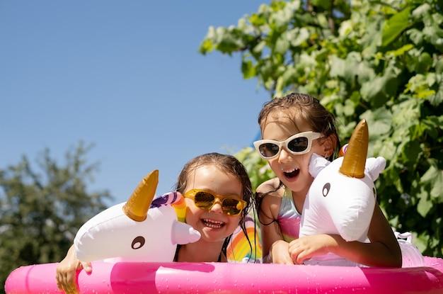 Dwie dziewczyny w okularach przeciwsłonecznych bawią się w dmuchanym basenie z kółkiem w kształcie jednorożca