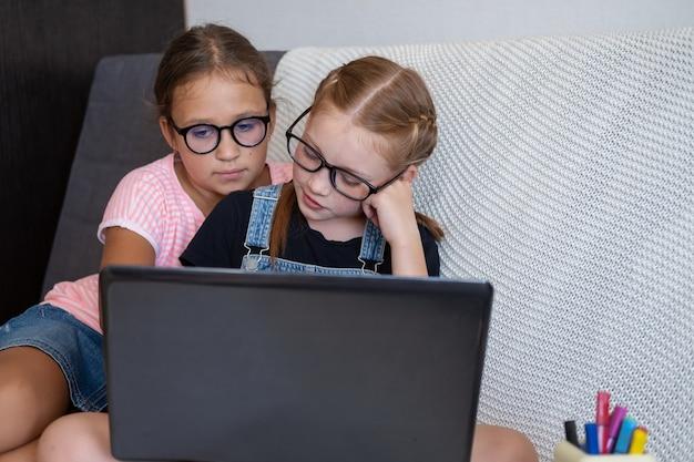 Dwie dziewczyny w okularach za pomocą laptopa podczas nauki w domu. usiądź na kanapie. powrót do koncepcji szkoły.