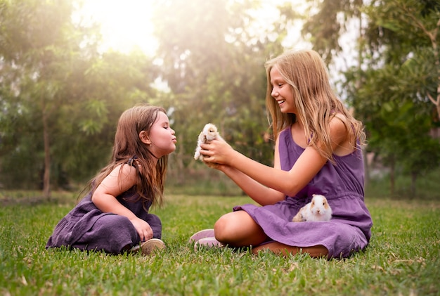 Dwie dziewczyny w parku bawiące się z królikami.