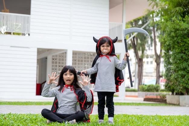Dwie dziewczyny w parku z kostiumami na halloween, bawią się