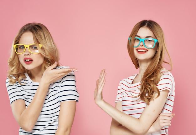 Dwie dziewczyny w paski koszulki z różowymi okularami przeciwsłonecznymi