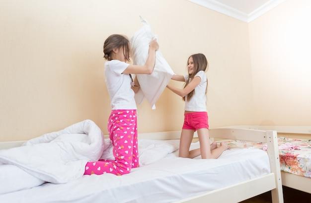 Dwie dziewczyny w piżamie walczące na poduszki