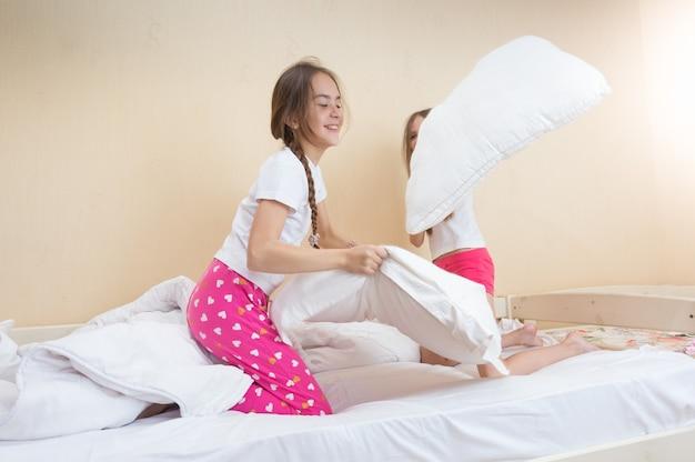 Dwie dziewczyny w piżamie walczące z poduszkami na łóżku