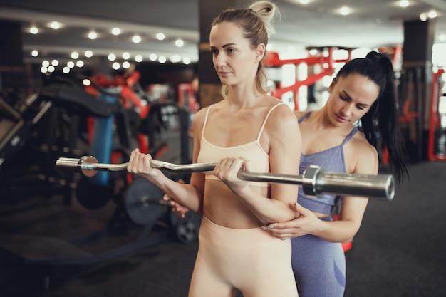 Dwie dziewczyny w średnim wieku są zaangażowane w siłownię. trener dziewczyna pomaga w treningu. podnoszenie poprzeczki na bicepsy