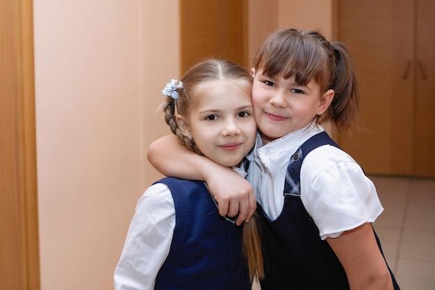 Dwie dziewczyny w szkole podstawowej w mundurze pozowanie na kamery. szkoła podstawowa. selektywna ostrość.