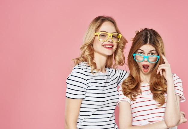 Dwie dziewczyny w t-shirtach w paski obejmują radość komunikacji moda luksusowy przycięty widok różowe tło