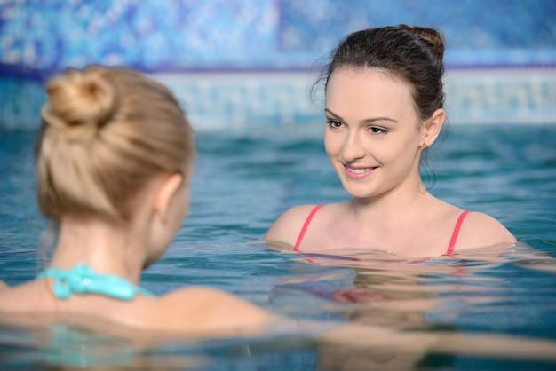 Dwie dziewczyny wdrapały się na basen i pływały.