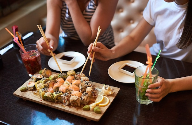 Dwie dziewczyny yang jedzą pyszne toczone sushi w restauracji serwowane na drewnianej desce z pałeczkami, sosem sojowym i koktajlami