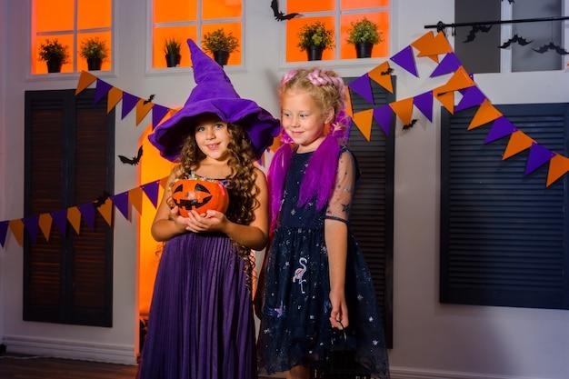 Dwie dziewczyny z dynią pełną słodyczy na wianku z flag wiszących na ścianie