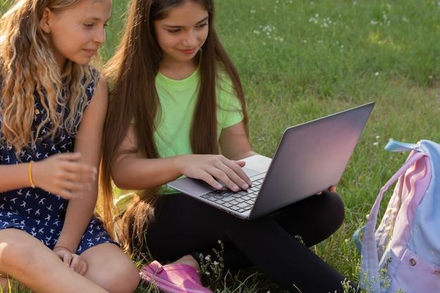 Dwie dziewczyny z laptopem i plecakiem odrabiają pracę domową lub bawią się siedząc na trawie na zewnątrz