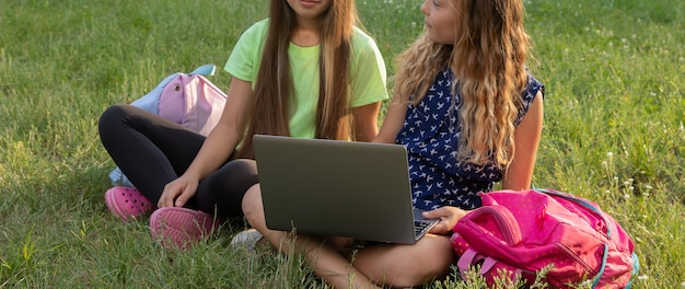 Dwie dziewczyny z laptopem i teczkami odrabiają pracę domową lub bawią się siedząc na trawie na zewnątrz